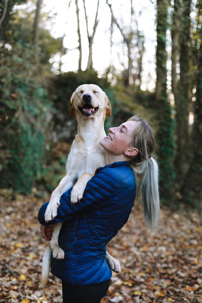 smiling white lab being hugged by a woman in the forest - Pawsitive Care Animal Hospital, Manassas, Virginia veterinarian